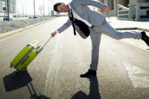 Mann mit Koffer glücklich